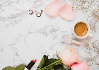 Earrings; lipstick; roses; nail varnish bottle; coffee cup and baby's-breath flower on textured background