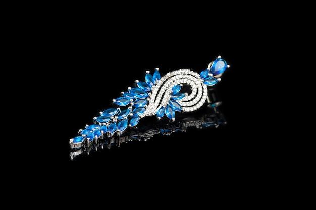 黒、クローズアップに分離された青い石のイヤリング