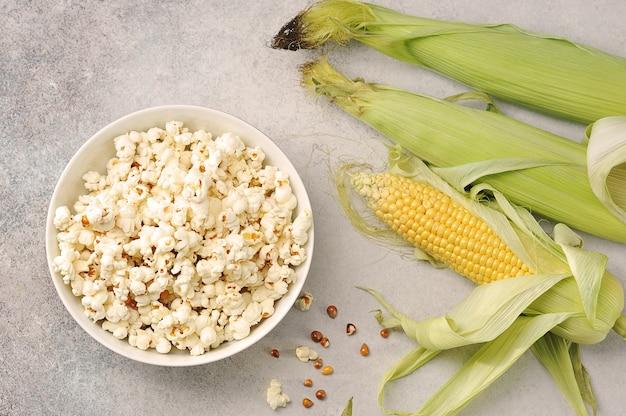 Ушки кукурузы и приготовленный попкорн в миске на сером