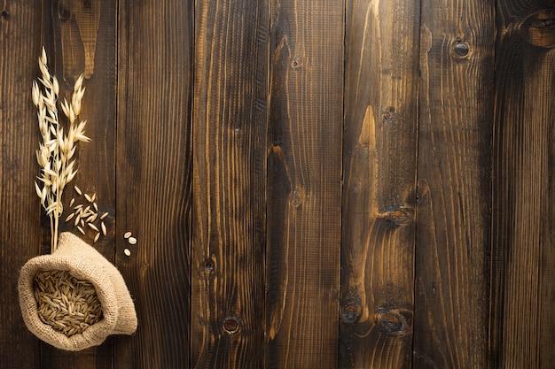 木製の背景にオーツ麦の耳