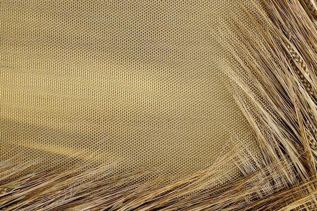 Колосья спелой ржи на золотой сетке на солнце. фон в виде колосьев ржи, разложенных с двух сторон солнечным пятном.