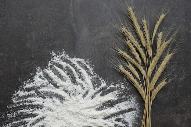 灰色の背景に小麦と小麦粉の耳。平面図、穀物。