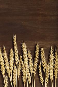 小麦の穂は暗褐色の木製の背景にクローズアップ収穫時期の概念穀物作物