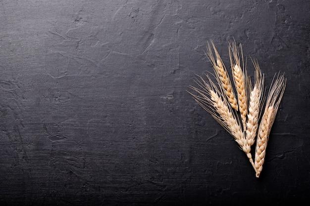 Колосья пшеницы на черном каменном фоне