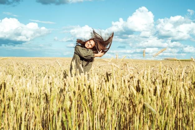 Колосья пшеницы. молодая девушка в платье показывает эмоции. эмоционально прыгает и бегает по летнему полю с колосками.