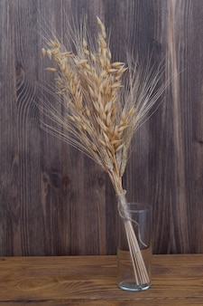 Ears of wheat and barley in a glass vase on the background of wooden boards.