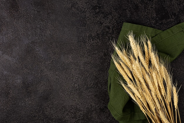Ears of wheat on black background texture. copyspace. top view. ears of corn on a green linen napkin