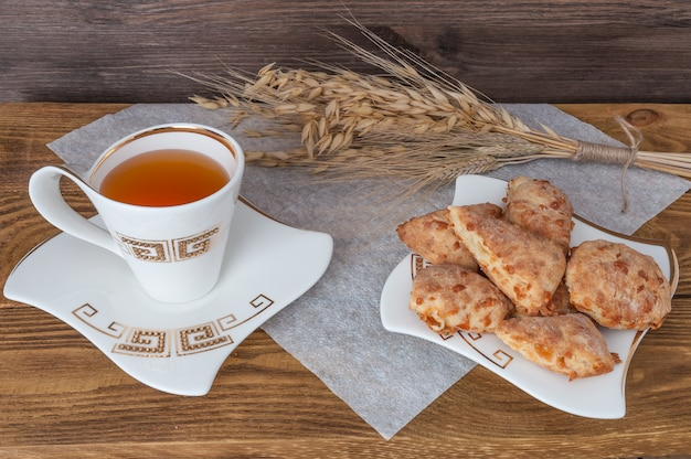 Ears of wheat, a cup of tea and biscuits on a wooden background