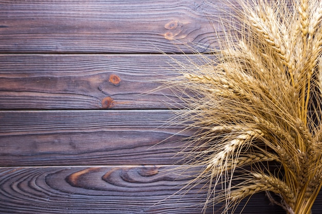 Ears of wheat on old wooden table