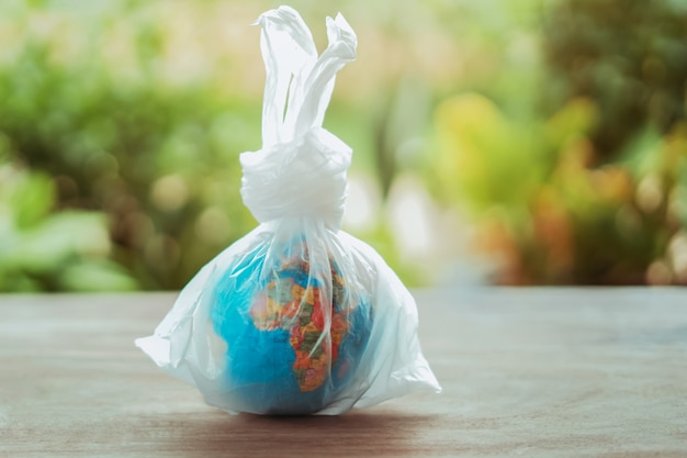 Earth day concept globe in plastic bag on table