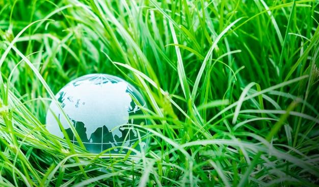 Концепция дня земли земного шара на зеленой траве с копией пространства