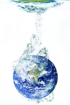 Earth falling in water on white