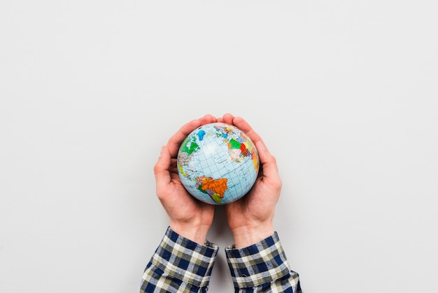 Earth globe in hands on grey background