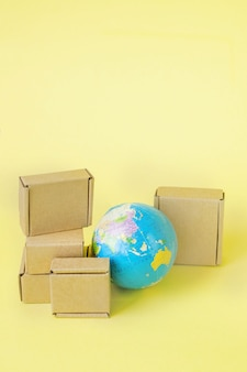 Земной шар окружен коробками. глобальный бизнес и международные перевозки грузовых продуктов. морские перевозки грузов, мировая торговля и экономика. распространение, импорт-экспорт. товарооборот.