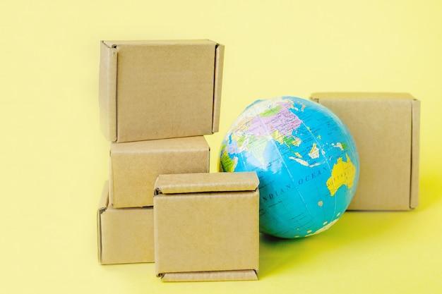 지구 지구는 상자로 둘러싸여 있습니다. 글로벌 비즈니스 및 상품의 국제 운송. 화물 운송, 세계 무역 및 경제학. 유통, 수입 수출. 상품 회전율.