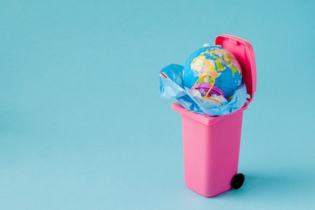Earth globe lies in the trash. plastic pollution concept
