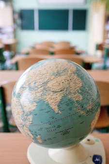 Earth globe model ball map with class room background. concept for global international educaiton or communications, politics environmental for learning world wide. vintage tone.