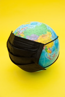 Earth globe model with black surgical mask isolated
