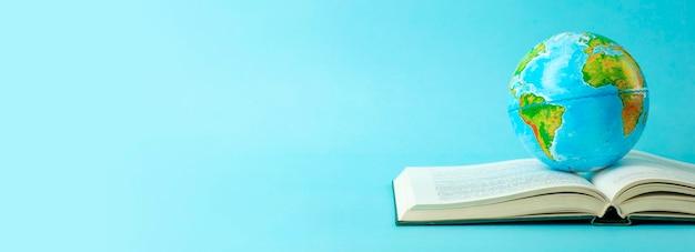 열려있는 책에 지구 지구입니다. 지식, 학습, 연구 개념