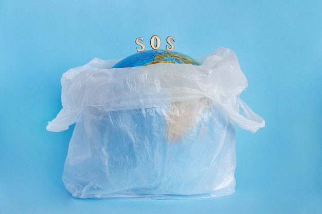 Earth globe in plastic bag and inscription sos, blue background. concept