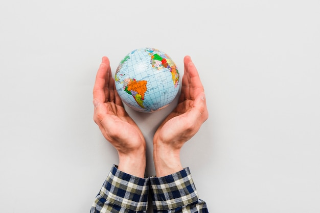 Earth globe surrounded by hands