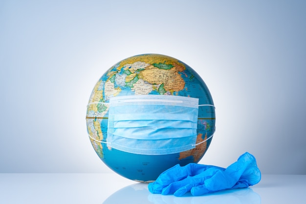 Earth globe with medical mask on next to a pair of surgical gloves