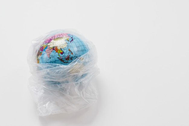 Earth globe wrapped in trash plastic bag