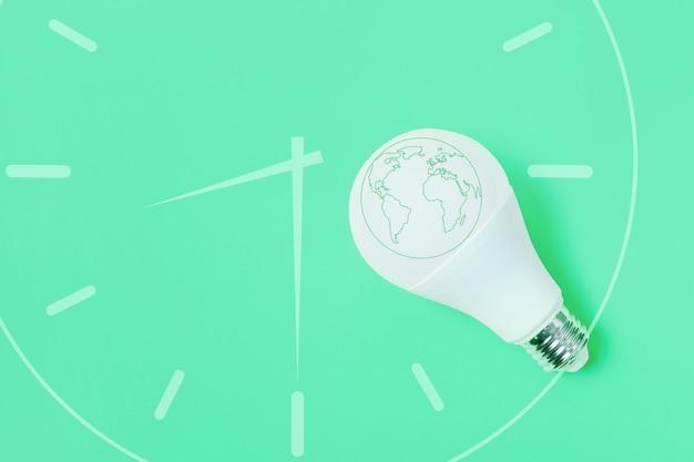 Концепция час земли. светодиодная лампа на зеленом