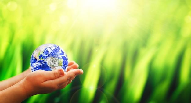 子供の手の中にある地球惑星保存と保護地球環境の概念世界アースデイ