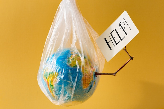 Earth in a plastic bag  holds card with the inscription help