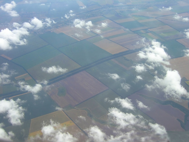 The earth's surface was taken from the height of the aircraft. below - land parcels divided into parts against the background of small clouds