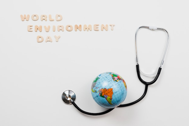 Earth over stethoscope and text world environment day