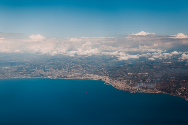Earth surface, sea coast and clouds, view from the airplane