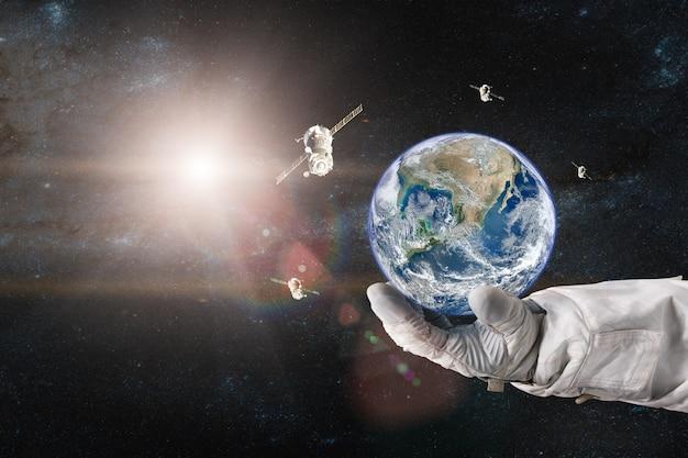 우주 비행사의 손에 우주선이 우주로 발사 된 지구