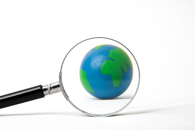 Earth with magnifying glass on white
