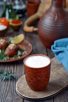 Глиняный стакан с холодным кефиром на деревянном столе