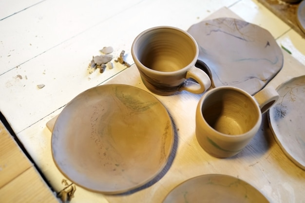Earthenware, ceramic mug, bowl, plate, cup on a wooden table