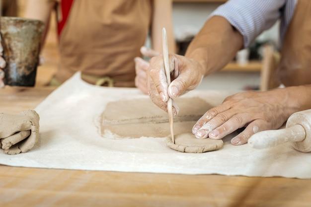 陶器サークル。作業室での作業中に手で小さな陶器の輪を形成するプロの陶芸家