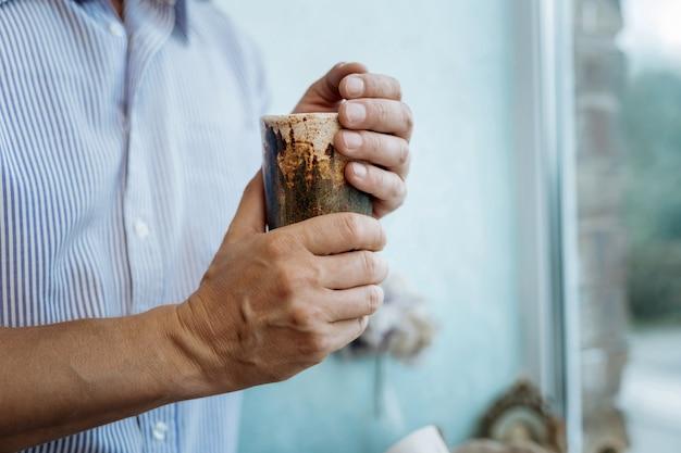 陶器カップ。お茶を片手に陶器のコップを持って窓際に立っている男
