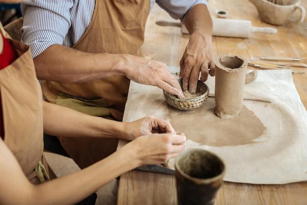 陶器のアイテム。彼の妻と一緒に陶器のアイテムを作る縞模様のシャツを着ている強い成熟した男