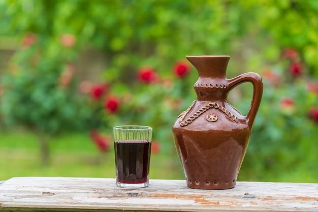 木製のテーブルの上の夏の庭の背景に陶器の水差しと赤ワインのガラス、クローズアップ