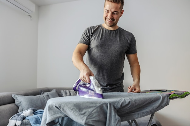 The ease of ironing laundry by a young smiling man