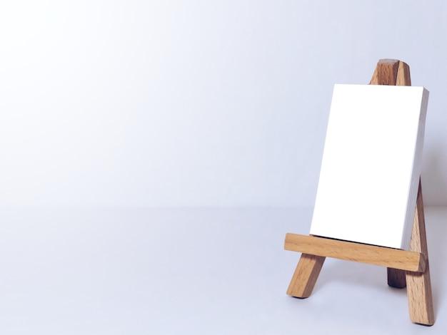 アーティストのためのイーゼルと白い背景の空白のキャンバスのミニチュア。