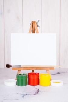 Easel, paint, gouache, paint brush. place for inscription, mockup