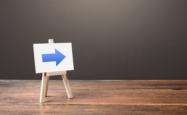 파란색 오른쪽 화살표가있는 이젤. 방향 표시. 상점 또는 아울렛 위치 광고
