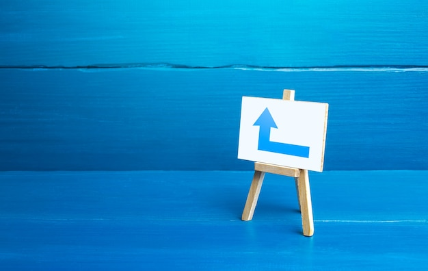 Easel with a blue left arrow minimalism direction to go around on the left advertising