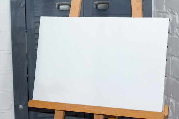 An easel with a clean white canvas is ready for work against a white brick wall