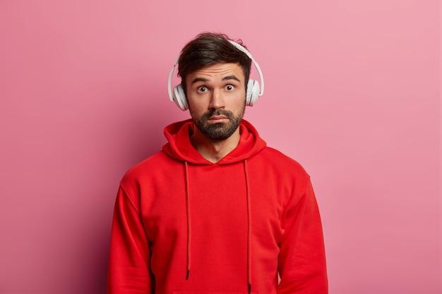 Un uomo facilmente impressionato che è stupito dall'espressione terrificante, reagisce a nuove voci sorprendenti, ascolta la traccia audio, indossa una felpa con cappuccio rossa, posa su un muro rosa pastello. persone, concetto di tempo libero