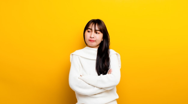 Easily upset portrait of an asian girl casual upset with folded arms looking out lonely. on a yellow background