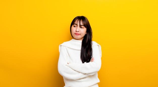 쉽게 화가 아시아 여자의 초상화 외로운 찾고 접힌 팔으로 캐주얼 화가입니다. 노란색 바탕에